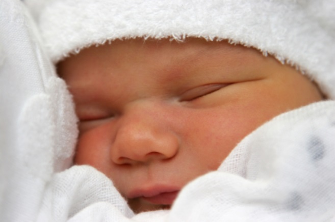 A newborn baby snuggling into white linen