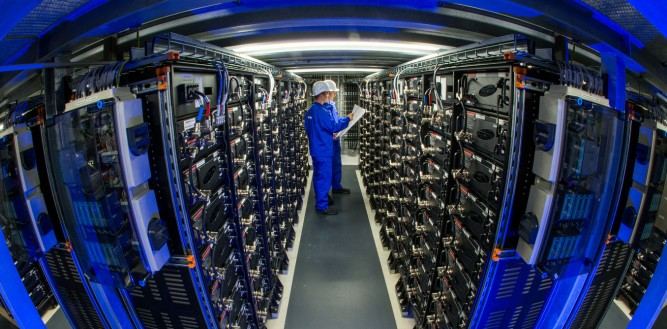 epaselect epa04399848 A picture made available on 14 September 2014 shows trainees Philipp Bathke (L) and Alexander Klatt between rows of energy storage devices at Europe's biggest commercial battery storage in Schwerin, Germany, 10 September 2014. The five megawatt facility was built by German power company WEMAG and will be ceremonially put online on 16 September 2014. It will help to stabilize the power grid.  EPA/JENS BUETTNER