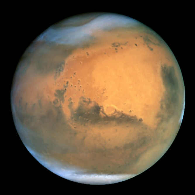 Frosty white water ice clouds and swirling orange dust storms above a vivid rusty landscape reveal Mars as a dynamic planet in this sharpest view ever obtained by an Earth-based telescope. The Earth-orbiting Hubble telescope snapped this picture on June 26, when Mars was approximately 43 million miles (68 million km) from Earth - its closest approach to our planet since 1988. Hubble can see details as small as 10 miles (16 km) across. Especially striking is the large amount of seasonal dust storm activity seen in this image. One large storm system is churning high above the northern polar cap [top of image], and a smaller dust storm cloud can be seen nearby. Another large duststorm is spilling out of the giant Hellas impact basin in the Southern Hemisphere [lower right]. Acknowledgements: J. Bell (Cornell U.), P. James (U. Toledo), M. Wolff (Space Science Institute), A. Lubenow (STScI), J. Neubert (MIT/Cornell)